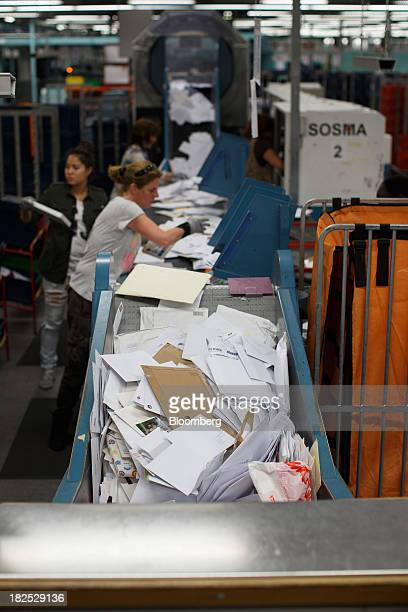 Employees stand beside a conveyor belt as letters and packages are sorted at the PostNL NV mail sorting center in Nieuwegein Netherlands on Friday...