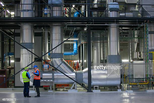 Employees stand beside the pipework of a coffee bean roaster as it stands in a hall at the Nestle SA factory in Schwerin Germany on Thursday Oct 16...