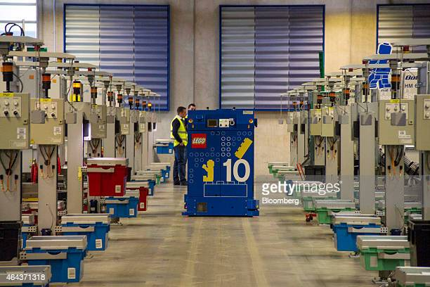 Employees stand between moulding machines in the manufacturing plant at the headquarters of Lego A/S in Billund Denmark on Wednesday Feb 25 2015 Lego...