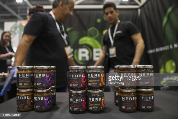 Employees stand by jars of HERBL peanut butter and jams at the CBD Hive stand at the Europe CBD Expo at the Excel in London UK on Friday Jul 12 2019...