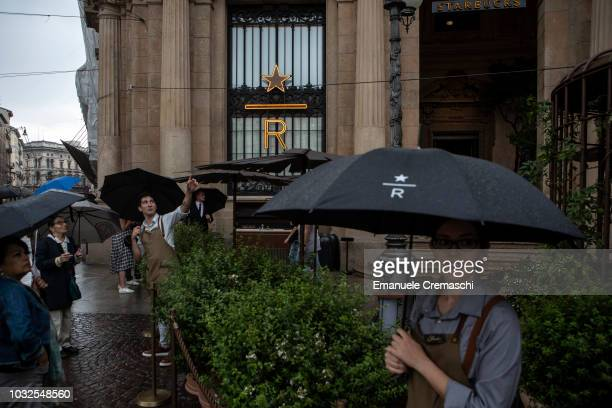 Employees stand during the opening of Europe's largest and Italy's first Starbucks Reserve Roastery located inside a historic post office in Piazza...