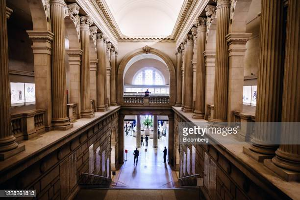 Employees stand guard as visitors gather at the entrance hall during the public reopening at the Metropolitan Museum of Art in New York, U.S., on...