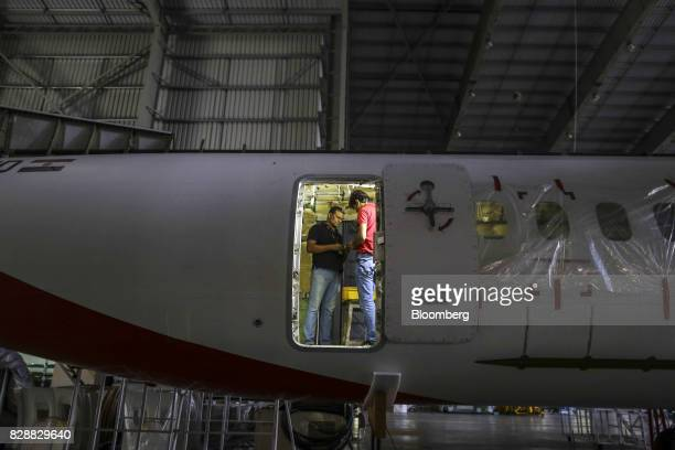 Employees stand illuminated in a doorway of a Bombardier Inc Q400 NextGen passenger aircraft undergoing maintenance at the Air Works Engineering Pvt...