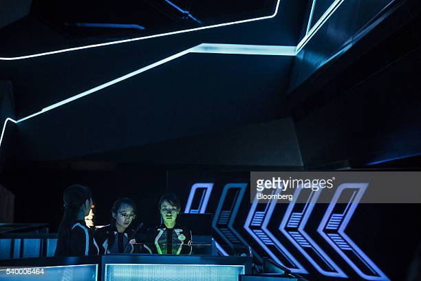 Employees stand in the waiting area for the Tron Lightcyle Power Run rollercoaster at Walt Disney Co's Shanghai Disneyland theme park during a trial...