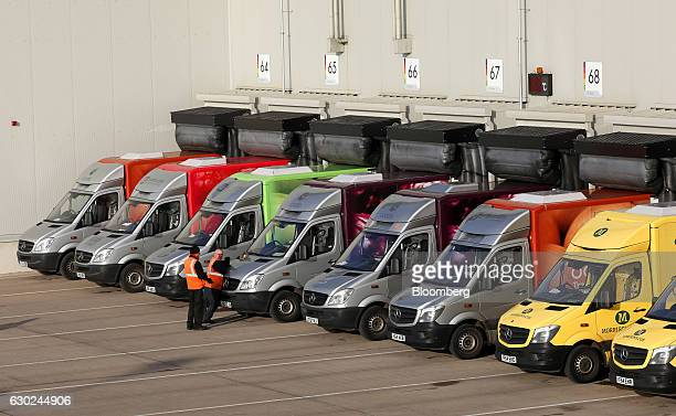 Employees stand next to a line of customer delivery vehicles at the Ocado Group Plc distribution centre in Dordon UK on Friday Dec 16 2016 Ocado...