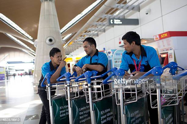 Employees stand next to buggies at Kuala Lumpur International Airport in Sepang Malaysia on Saturday July 19 2014 Flags in Malaysia flew at halfmast...