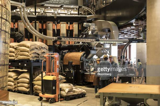 Employees stand next to coffee beanroasting equipment inside the Starbucks Corp Reserve Roastery store in Shanghai China on Friday May 11 2018...