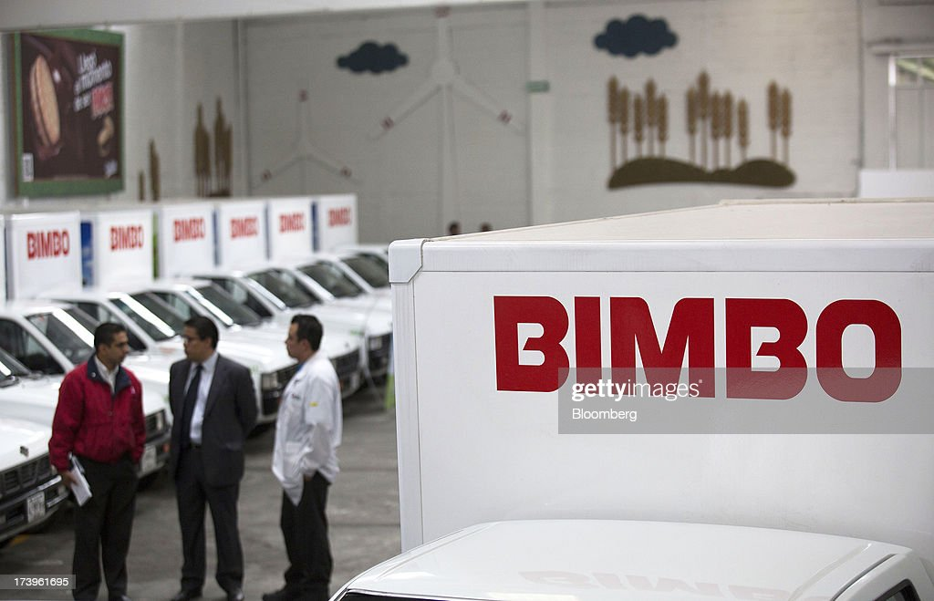 Employees stand next to electric delivery trucks inside Grupo Bimbo SAB de CV's new sales center in Mexico City, Mexico, on Thursday, July 18, 2013. Grupo Bimbo inaugurated a new eco-friendly sales center today. Photographer: Susana Gonzalez/Bloomberg via Getty Images