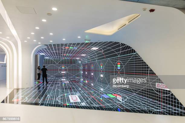 Employees stand on a digital screen at a showroom inside the JDcom Inc headquarters in Beijing China on Monday Oct 23 2017 JDcom isChina's...