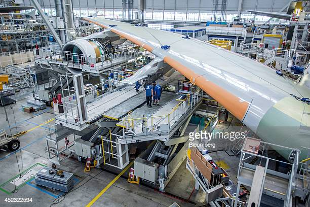 Employees stand on a platform beneath the wing of a Airbus A380 aircraft on the assembly line at the Airbus Group NV factory in Toulouse France on...