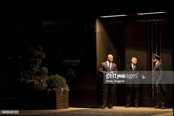 Employees stand outside of Trump SoHo hotel condominium building February 21 2017 in New York City The development of Trump SoHo completed in 2010...