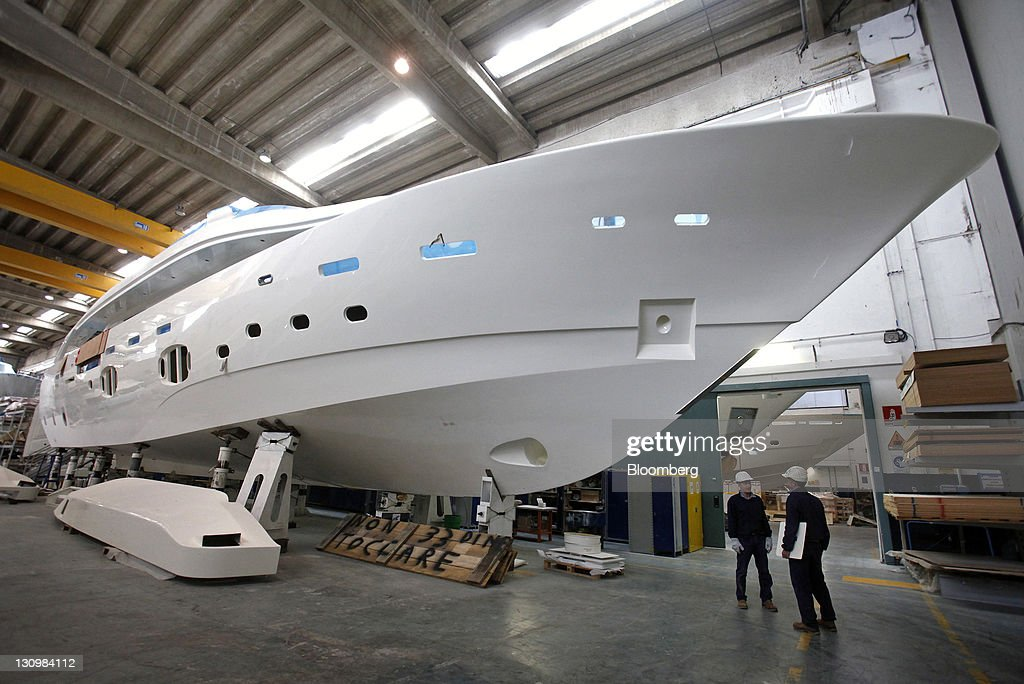 Employees Stand Underneath A Custom Line Navetta 33 Crescendo Yacht Inside Warehouse At