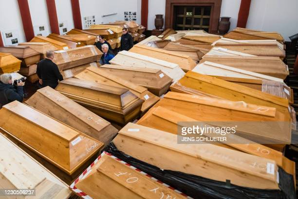 Employees store coffins among many others in the mourning hall of the crematorium in Meissen, eastern Germany, on January 13, 2021. - Most of the...