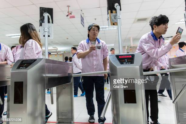 Employees swipe their id cards and stands in front of a facial recognition system before they are allowed onto the assembly line area at a Pegatron...
