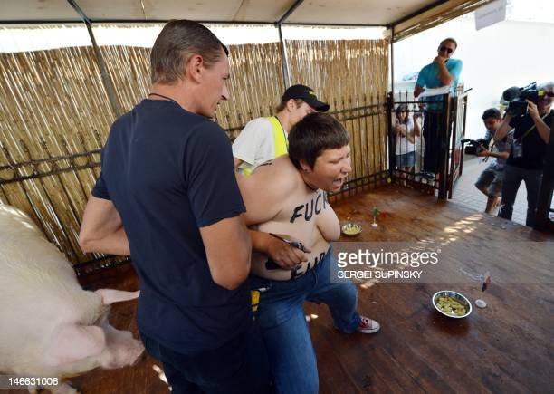 Employees take away an activist of Ukrainian women movement Femen protesting in the cage Funtik the psychic pig in the Euro 2012 fanzone in Kiev on...