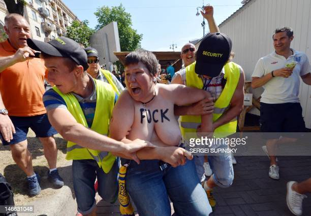 Employees take away an activist of Ukrainian women movement Femen protesting in the Euro 2012 fanzone in Kiev on June 21 2012 during the Euro 2012...