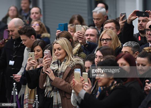 Employees take photos on their phones as Prince William Duke of Cambridge visits Bombardier Transportation where he looked at Crossrail carriage...