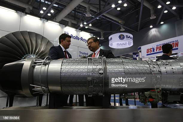 Employees talk behind a model of the Rolls-Royce Holdings Plc EJ200 jet engine at the Seoul International Aerospace & Defense Exhibition 2013 in...