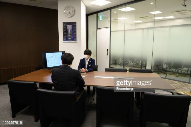 Employees talk during a media tour at a branch of Mizuho Bank Ltd. In Kawasaki, Kanagawa Prefecture, Japan, on Monday, Nov. 9, 2020. Japanese banks...