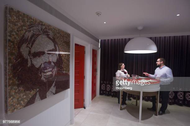 Employees talk inside a Virgin Money Lounge operated by Virgin Money Holdings Plc as a portrait of billionaire Richard Branson sits on display in...