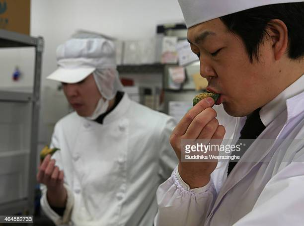Employees taste freshly made Japanese sweet named Samuchi, which are made by Azuki bean and Mochi at Amaneya sweet shop on January 23, 2014 in...