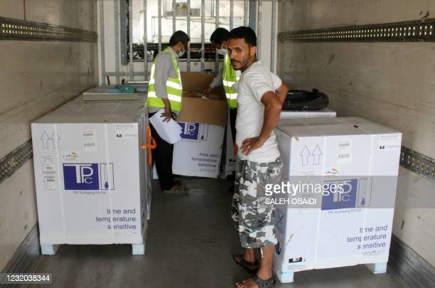 Employees transport boxes containing vials of the AstraZeneca/COVISHIELD vaccine against the coronavirus, upon the arrival of the first shipment at...