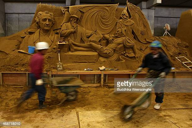 Employees transport waste sand front of the sand sculpture named 'German Literature Goethe and his work Faust' ahead of 'Germany and Once Upon a...