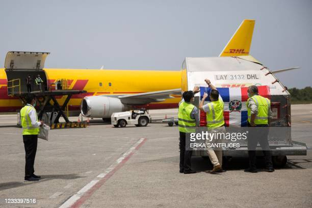 Employees unload shipping containers with 228,150 doses of the Pfizer-BioNTech vaccine against COVID-19, upon arrival at Las Americas Airport in...
