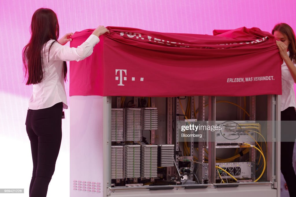 Employees unveil a multifunction primary connection point box at the Deutsche Telekom AG shareholders' meeting in Bonn, Germany, on Thursday, May 17, 2018. Deutsche Telekom and Daimler AG agreed to settle a 14-year-old arbitration case with the German government over the countrys truck toll system with a cash payment of 1.1 billion euros, the Transport Ministry said in a statement. Photographer: Alex Kraus/Bloomberg via Getty Images