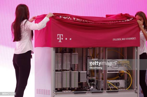 Employees unveil a multifunction primary connection point box at the Deutsche Telekom AG shareholders' meeting in Bonn Germany on Thursday May 17...
