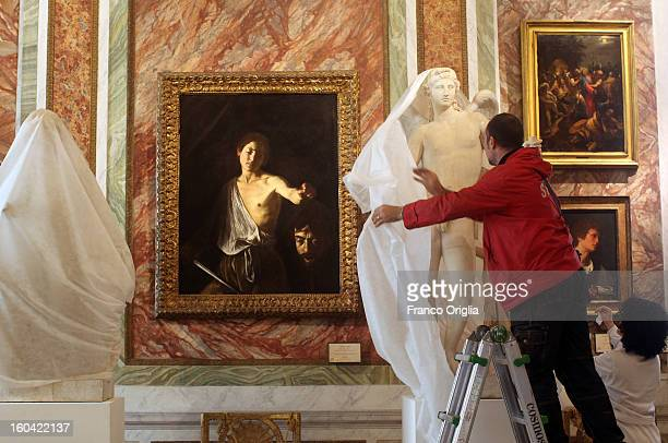 Employees unveil 'The Genius' a sculpture belonging to the Louvre museum in Rome for a temporary exhibition while 'David e Golia' painting by...