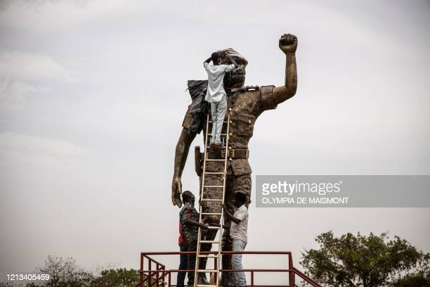 Employees unveil the second bronze statue of Burkina Faso's former President Thomas Sankara who was killed on October 15 at his memorial at the...