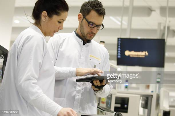 Employees use a touchscreen tablet device to control the automated driving Advanced Radar sensor mainboard production line at the Continental AG...