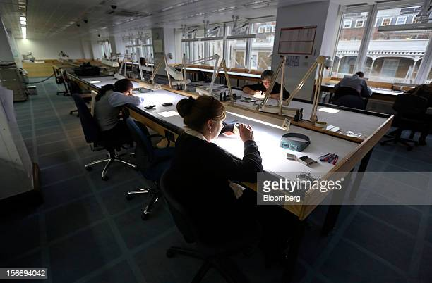 Employees use angled lights and magnifying glasses to sort uncut diamonds at the De Beers office in London UK on Friday Nov 16 2012 De Beers the...
