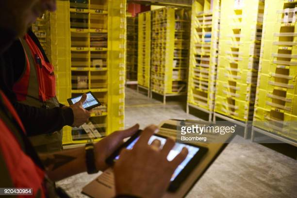 Employees use computer devices to control automated transport robots used to move shelving units containing goods around the robotics field area at...