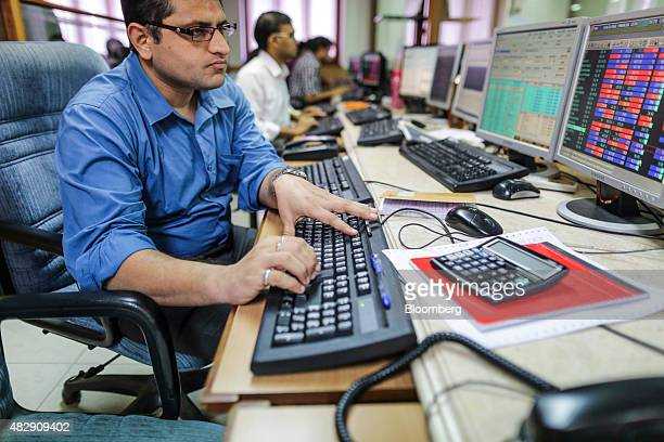 Employees use desktop computers as they monitor data at a securities brokerage in Mumbai India on Tuesday Aug 4 2015 Indian central bank Governor...