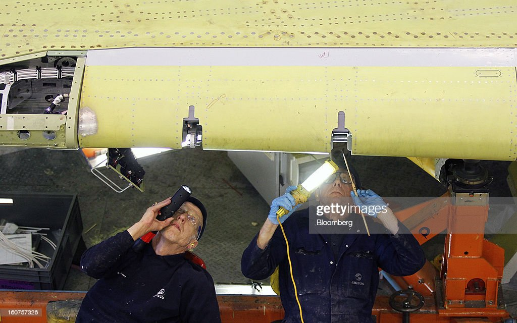 Employees use lights to inspect a mechanism on an Airbus A320 single-aisle passenger aircraft wing during production at the company's factory in Broughton, U.K., on Monday, Feb. 4, 2013. Airbus SAS won a $9 billion order from Steven Udvar-Hazy's Air Lease Corp. that includes 25 A350 wide-body jets, a competitor to Boeing Co.'s grounded 787 Dreamliner. Photographer: Paul Thomas/Bloomberg via Getty Images