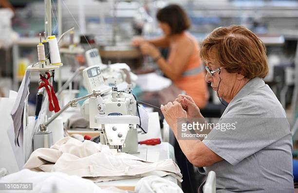 Employees use sewing machines as they work on luxury garments inside Brunello Cucinelli SpA's production facility in Solomeo near Perugia Italy on...
