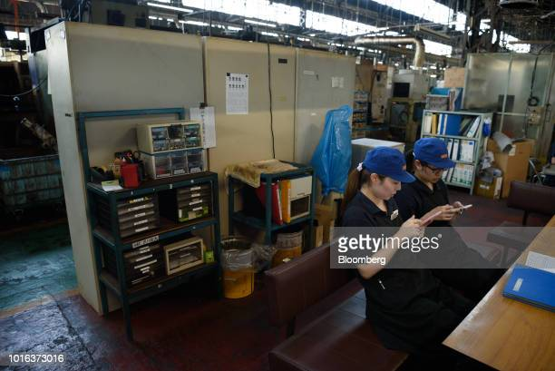 Employees use their smartphones while taking a break at an Asahi Tekko Co factory in Nishio Aichi Prefecture Japan on Wednesday Aug 1 2018 Japan's...
