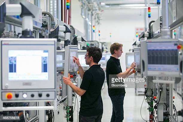 Employees use touchscreen panels on the automobile gasoline direct injector valve assembly line at the Robert Bosch GmbH plant in Blaichach Germany...