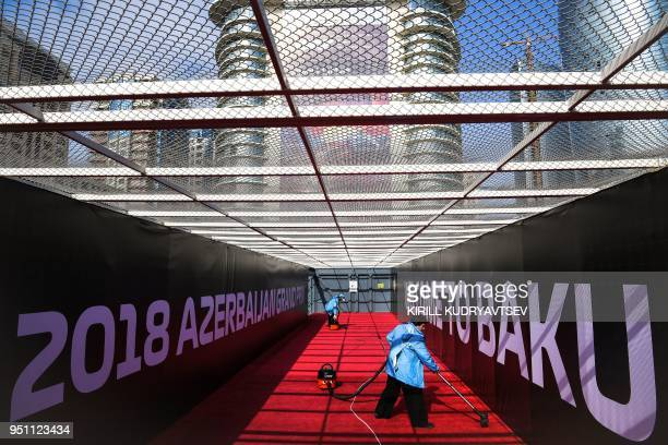 TOPSHOT Employees use vacuum cleaners to prepare a pedestrian overpass at the Baku City Circuit ahead of the Formula One Azerbaijan Grand Prix in...