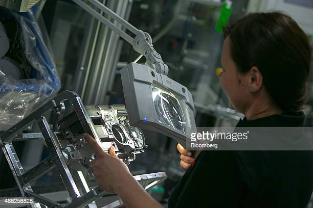 A employees uses a magnifying lens during quality control on the Bosch iBooster autonomous automobile braking assistance production line at the...