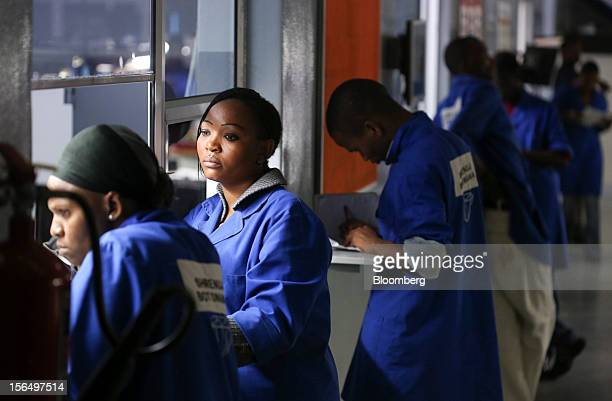 Employees wait at quality control windows to assess the grade of finished diamonds at the Shrenuj Botswana Ltd sightholder office in Gaborone...