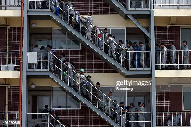 Employees wait in line to enter a canteen for lunch at the Hyundai Mipo Dockyard Co shipyard an affiliate of Hyundai Heavy Industries Co in Ulsan...