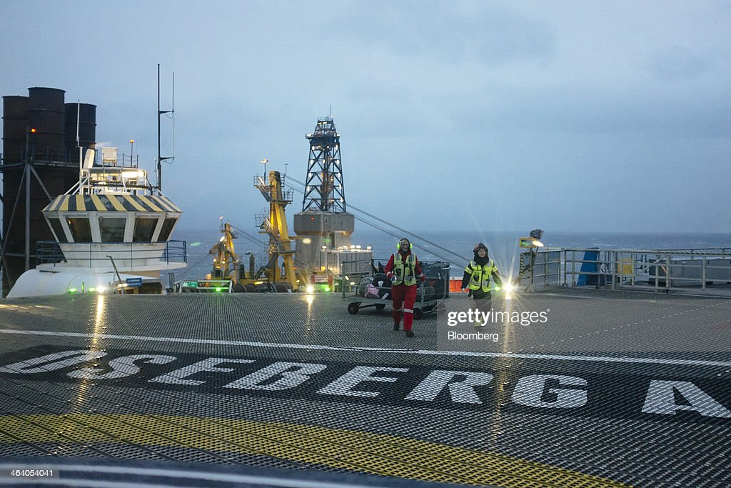 Employees walk across the helicopter pad on the Oseberg A offshore gas platform operated by Statoil ASA in the North Sea 140kms from Bergen, Norway, on Friday, Jan. 17, 2014. Statoil, Norway's biggest energy company, sees the potential to keep domestic oil and gas output at today's levels until 2025 and possibly beyond even as it tightens spending amid rising costs. Photographer: Kristian Helgesen/Bloomberg via Getty Images