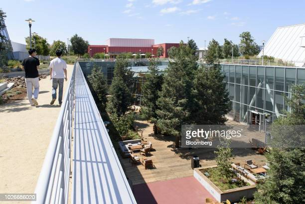 Employees walk along the green roof at the new Facebook Inc. Frank Gehry-designed MPK 21 office building in Menlo Park, California, U.S., on...