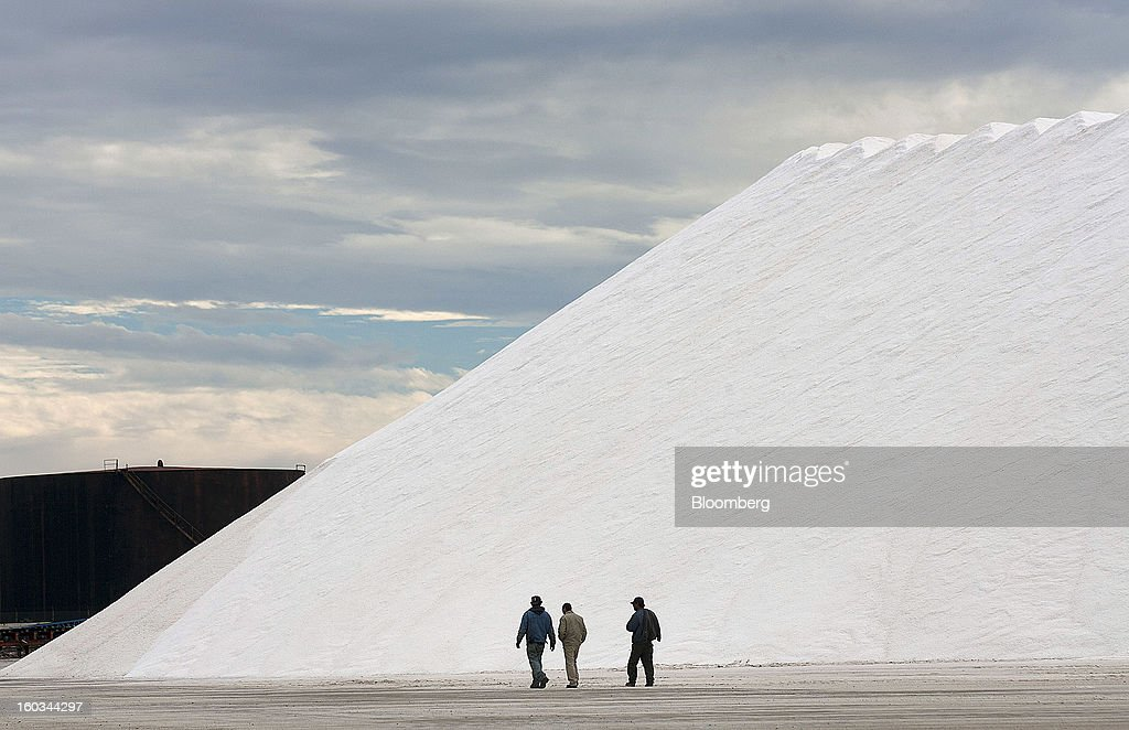 Employees walk beside a mountain of salt at the Exportadora de Sal (ESSA) salt-transshipment facility on Cedros Island off the coast of Guerrero Negro, Mexico, on Wednesday, Jan. 24. 2013. Exportadora de Sal (ESSA), a joint venture between Fidecomiso Mining Development Corporation and Mitsubishi, is one of the leading producers and suppliers of salt for the chlorine-alkali industry in the Pacific Rim. Photographer: Susana Gonzalez/Bloomberg via Getty Images
