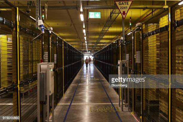 Employees walk between sections of the robotics field unit at Amazoncom Inc's new fulfillment center in Kolbaskowo Poland on Friday Feb 16 2018 Both...