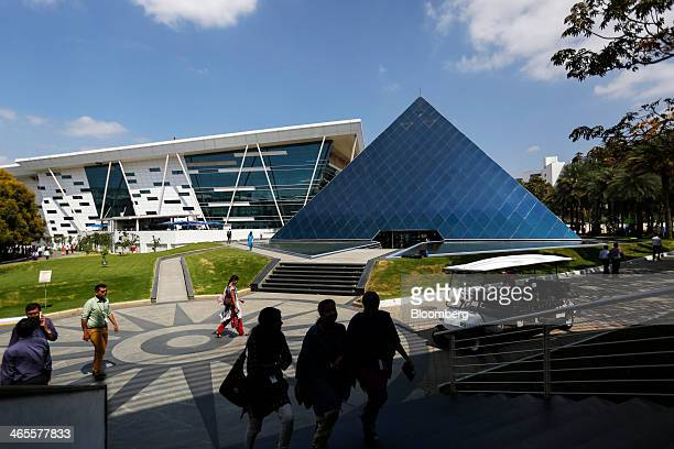 Employees walk near a pyramid shaped building at the Infosys Ltd campus in Electronics City in Bangalore India on Monday Jan 27 2013 Infosys India's...