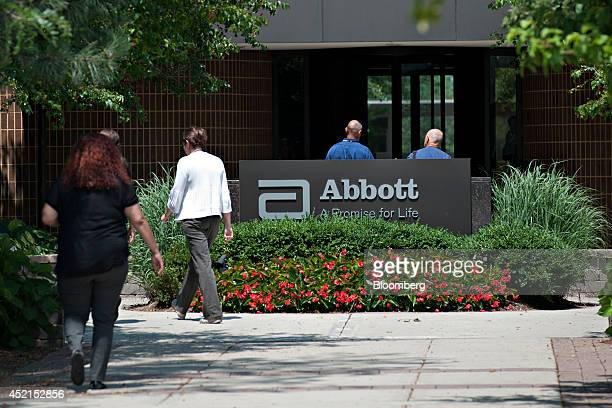 Employees walk near an Abbott Laboratories sign at the company's headquarters complex in Abbott Park Illinois US on Monday July 14 2014 Abbott...